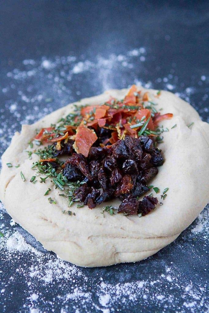 Chopped prunes and crispy prosciutto on focaccia dough.