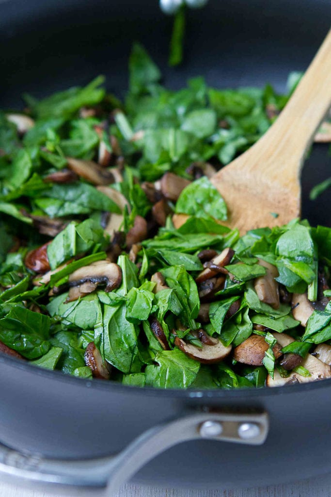 Sauteing spinach and mushrooms in a nonstick skillet.
