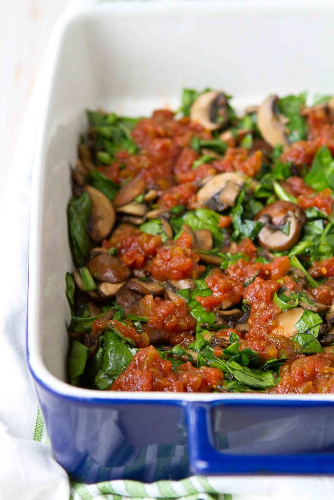 Mushrooms, spinach and salsa in a casserole dish.