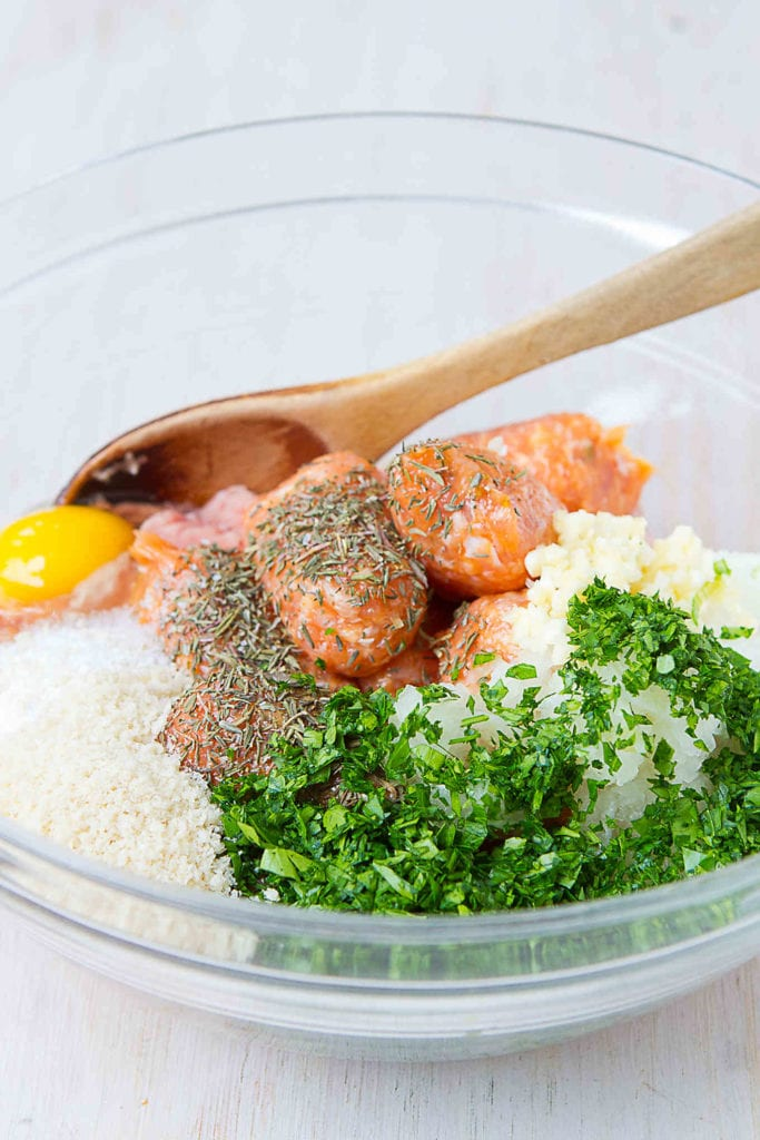 Chicken and turkey meatball ingredients in a glass bowl.
