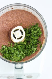 Black bean dip in a food processor, with chopped cilantro.