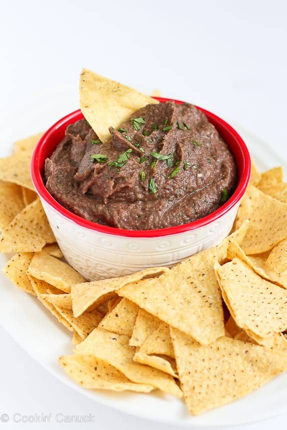 Black bean dip in a white bowl with red rim, on a plate with tortilla chips.