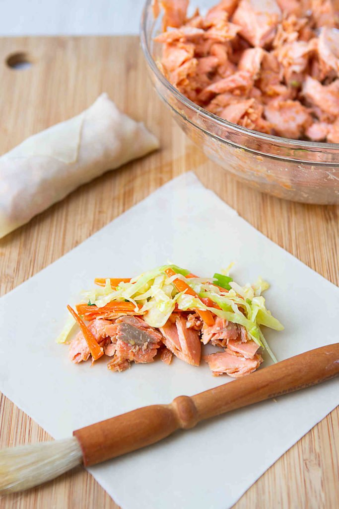 Cooked teriyaki salmon and cabbage mixture on an egg roll wrapper.