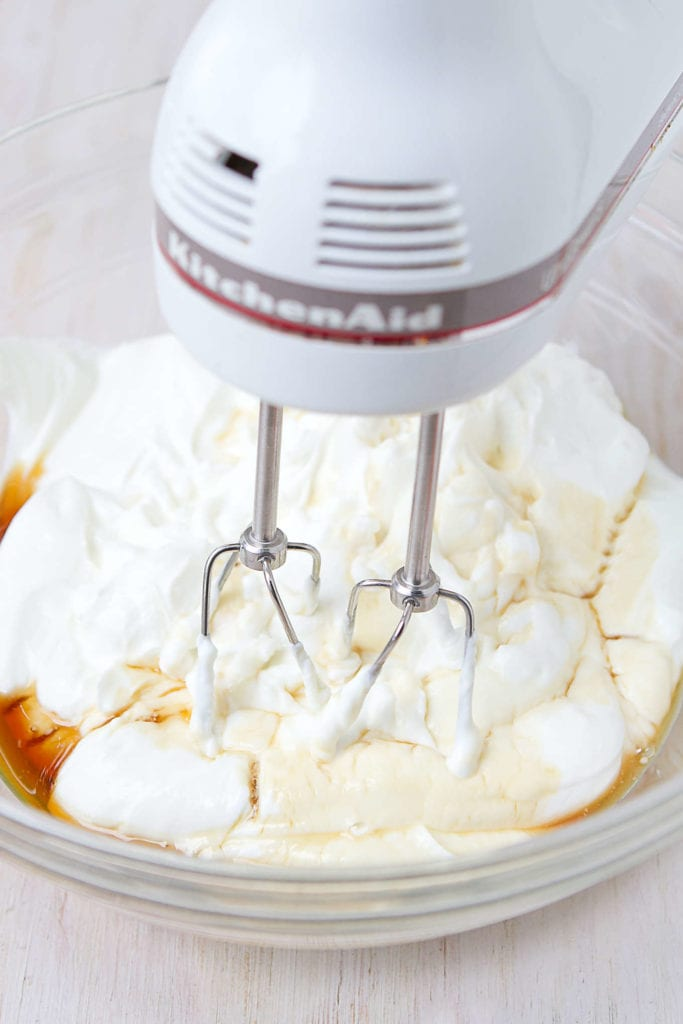 Whipping Greek yogurt with maple syrup and nutmeg until it is light and fluffy.