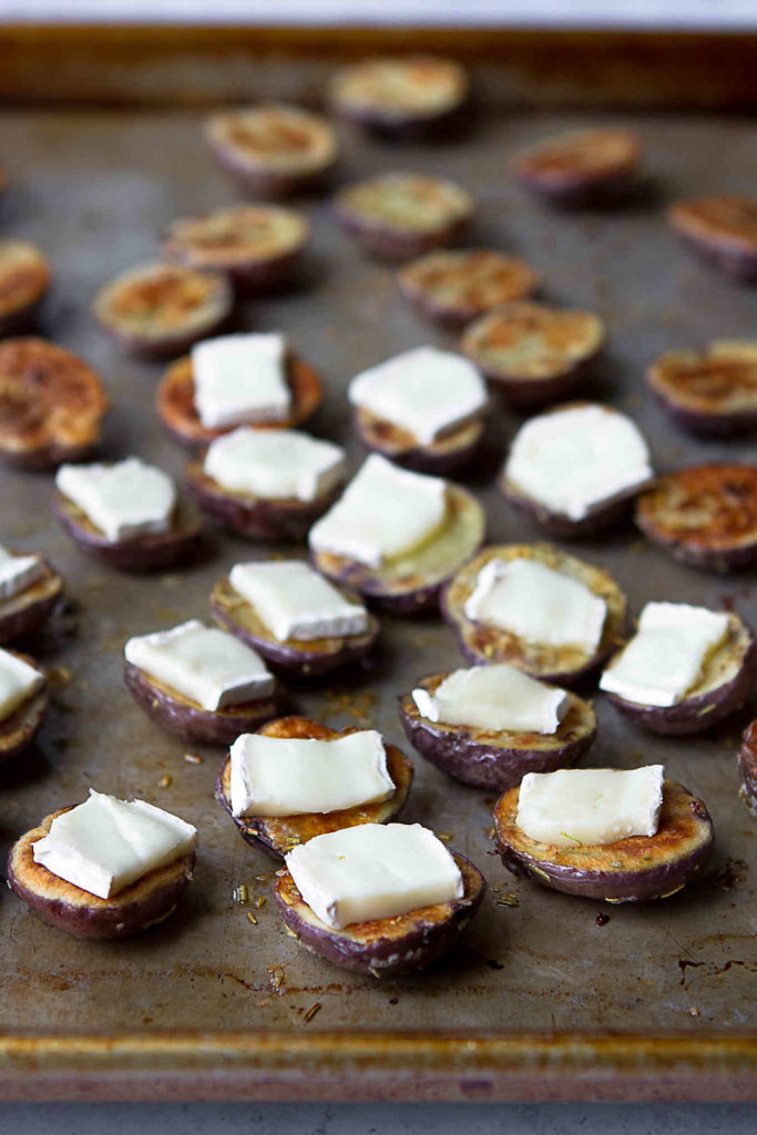 Little potatoes roasted on a baking sheet, each topped with a slice of Brie cheese.
