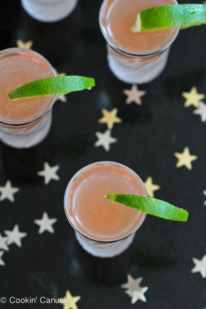 Overhead photo of cranberry juice vodka shots, on a black background with stars.