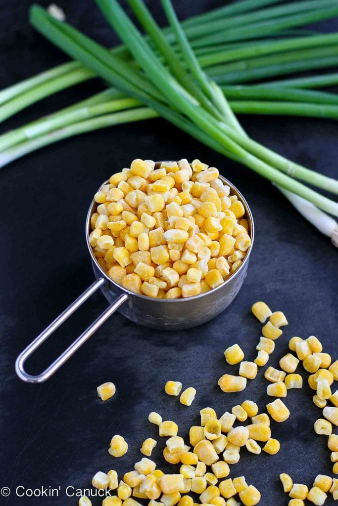 Frozen corn in a measuring cup, plus green onions.