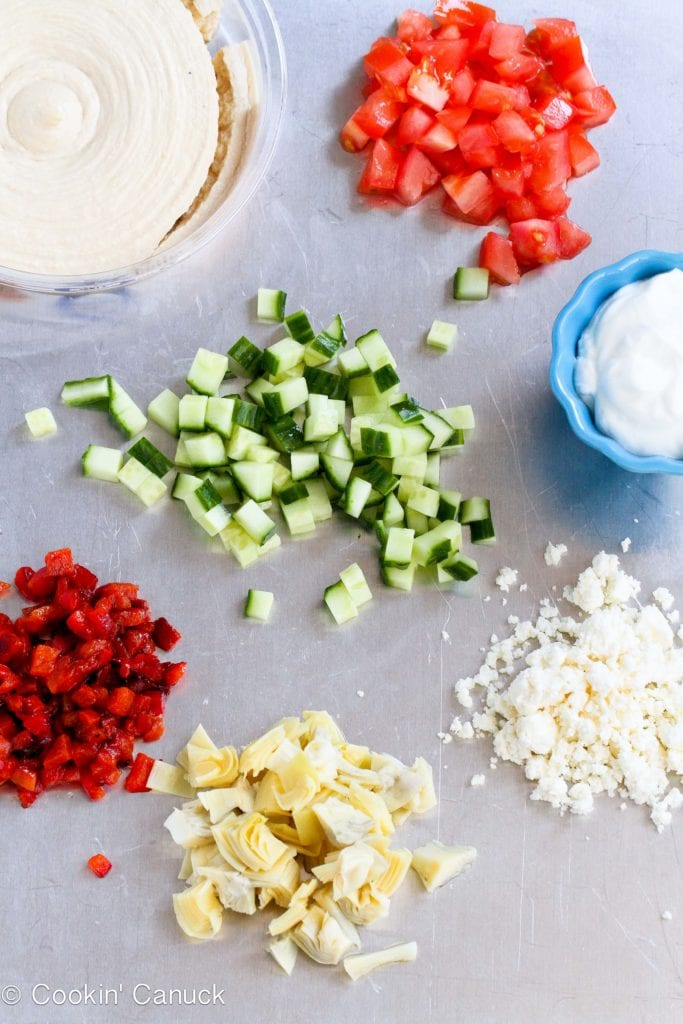 Chopped cucumber, tomatoes, roasted peppers, artichokes, feta cheese and yogurt on a baking sheet.