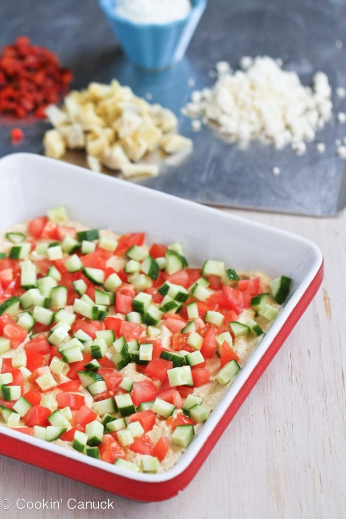 Layering cucumber, tomatoes, artichokes, feta cheese and roasted peppers in a serving dish.
