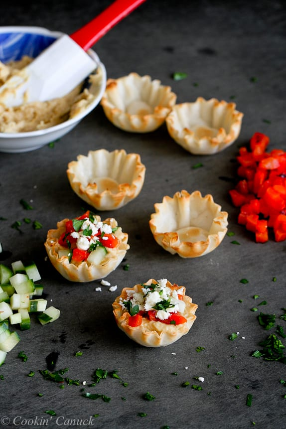 Filling mini phyllo cups with hummus, roasted peppers, cucumber and feta cheese.