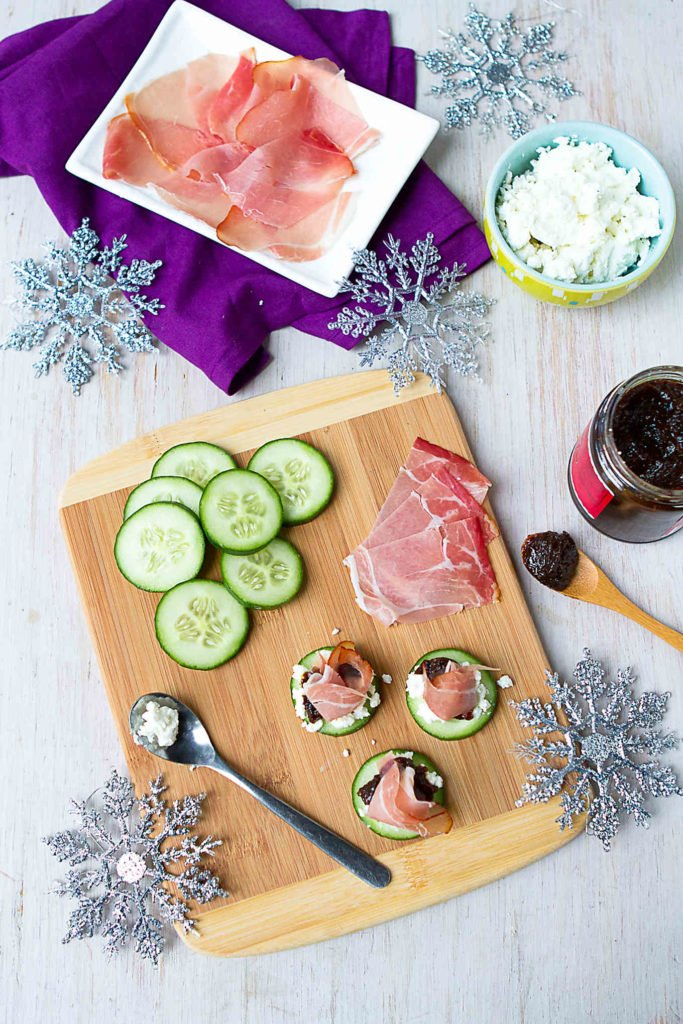 Putting together prosciutto, goat cheese and cucumber on a cutting board, assembling appetizers.