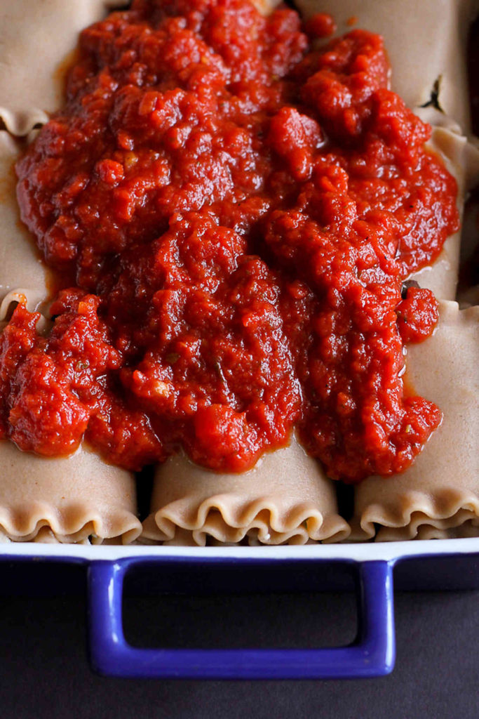 Lasagna rolls in a baking dish, covered in tomato sauce.