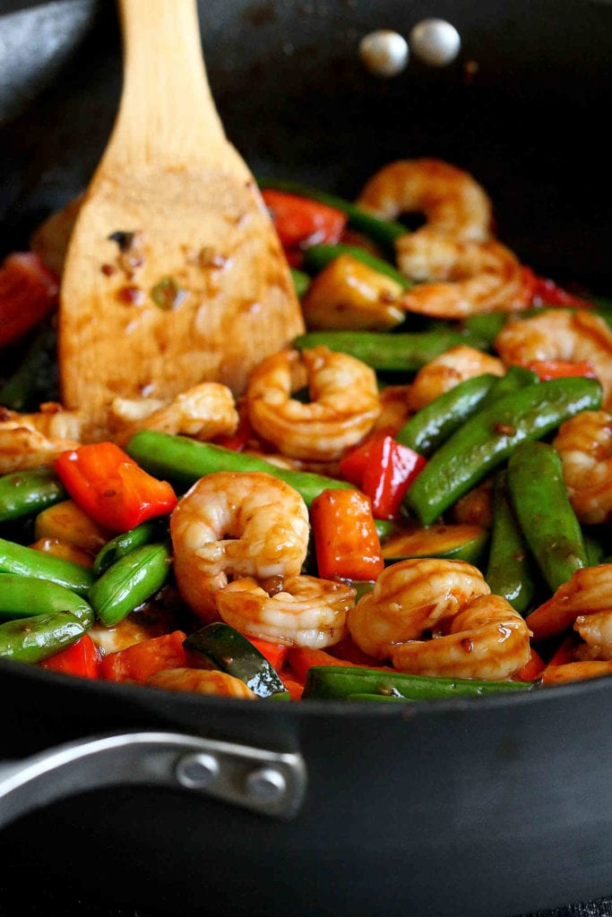 Shrimp, red bell peppers and snap peas being stir-fried in a nonstick skillet.