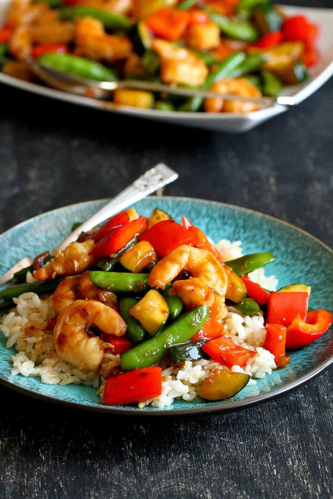 This shrimp stir fry recipe can be whipped up in minutes, is packed with veggies and served on a bed of aromatic jasmine rice. 309 calories and 6 Weight Watchers Freestyle SP #shrimp #stirfry #weightwatchers