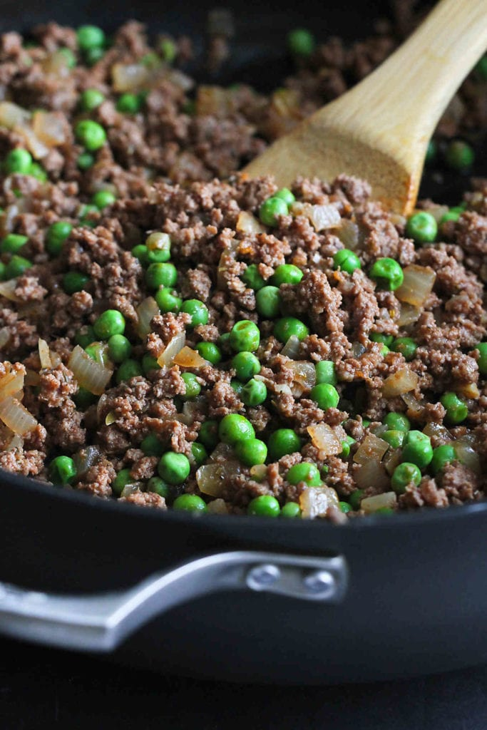 Cooked ground bison and green peas in a nonstick skillet.