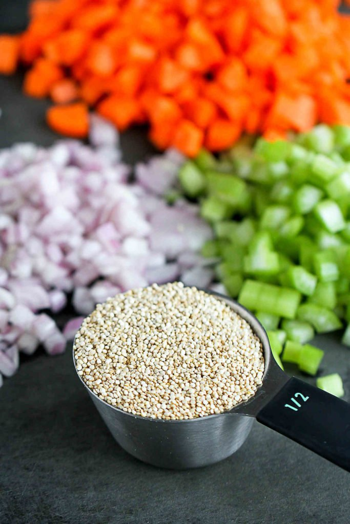 Dry quinoa, plus onions, carrot and celery on a cutting board.