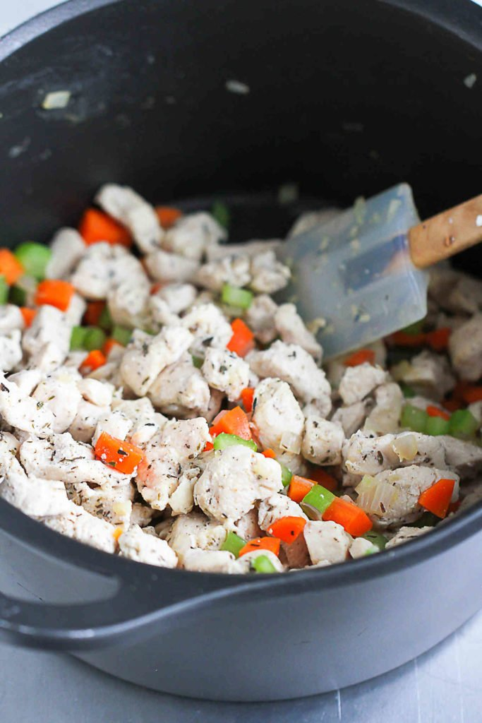 Sauteed chicken and vegetables in a saucepan.
