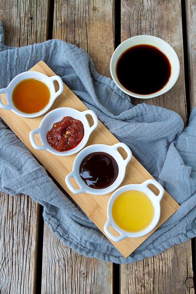 Stir fry sauce ingredients in small bowls, on a wooden table.