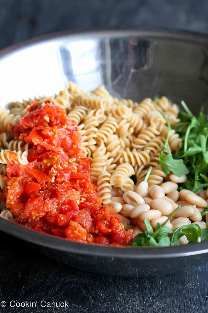 Cooked pasta, chopped roasted tomatoes, white beans and arugula in a large glass bowl.