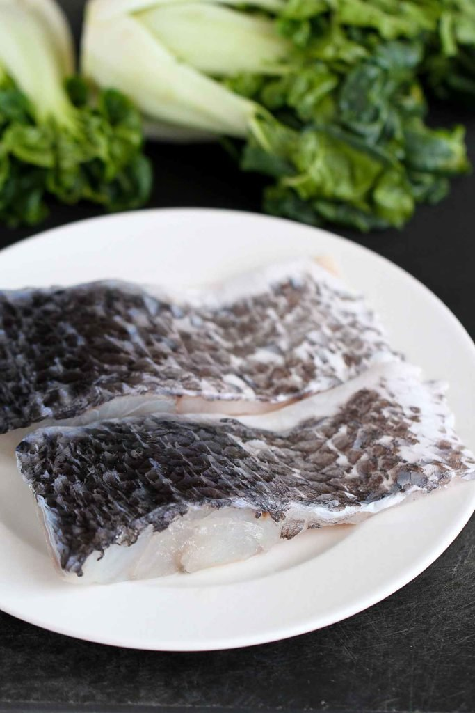 Barramundi (a white fish) fillets on a white plate, skin side up.