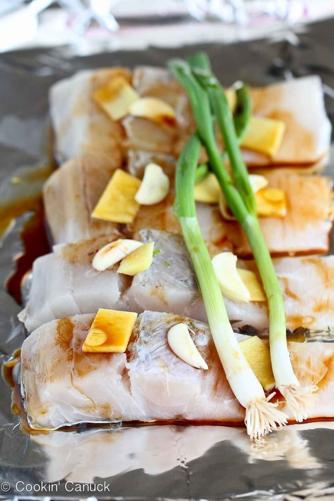 Fish fillets on foil, topped with soy sauce, ginger garlic and green onions.