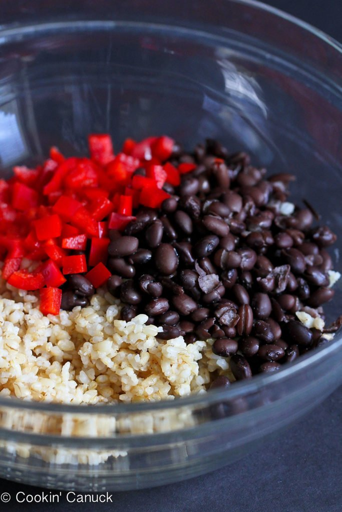 Brown rice, black beans and red bell peppers in a large glass bowl.