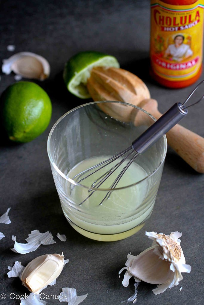 Lime juice in a glass with a whisk, surrounded by fresh lime, garlic and hot sauce.