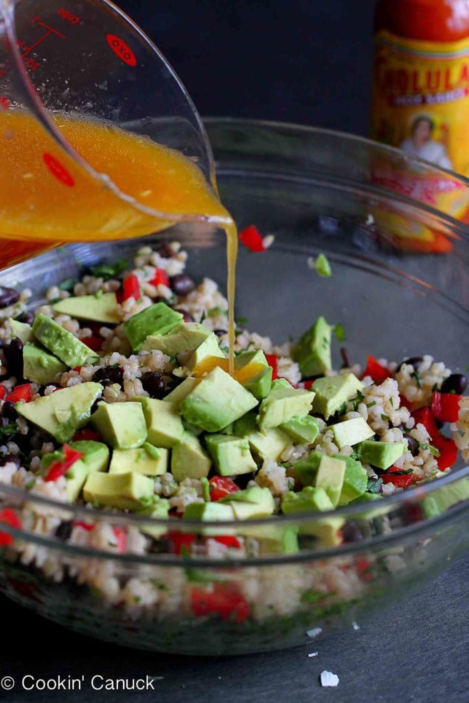 Pouring a hot sauce-based dressing over brown rice, avocado, black beans and red bell peppers in a large glass bowl.