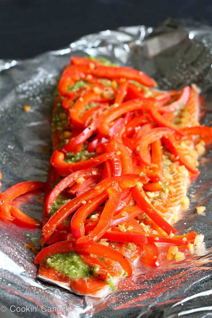 Cooked red bell pepper strips on a salmon fillet.