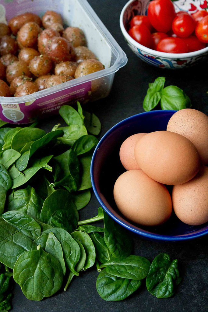 Egg, spinach, tomatoes and The Little Potato Company microwave potatoes, all on a black cutting board.