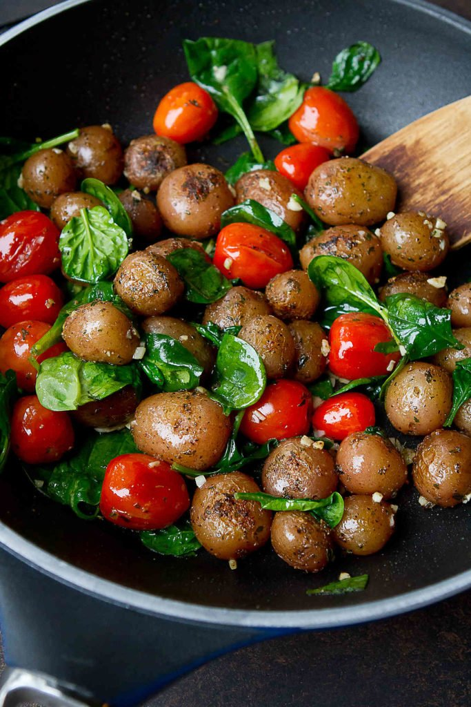Little potatoes, grape tomatoes and spinach in a large nonstick skillet.