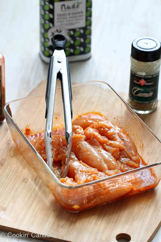 Chicken tenders and marinade in a glass container.