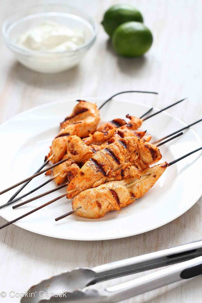 Grilled chicken tenders on wooden skewers.