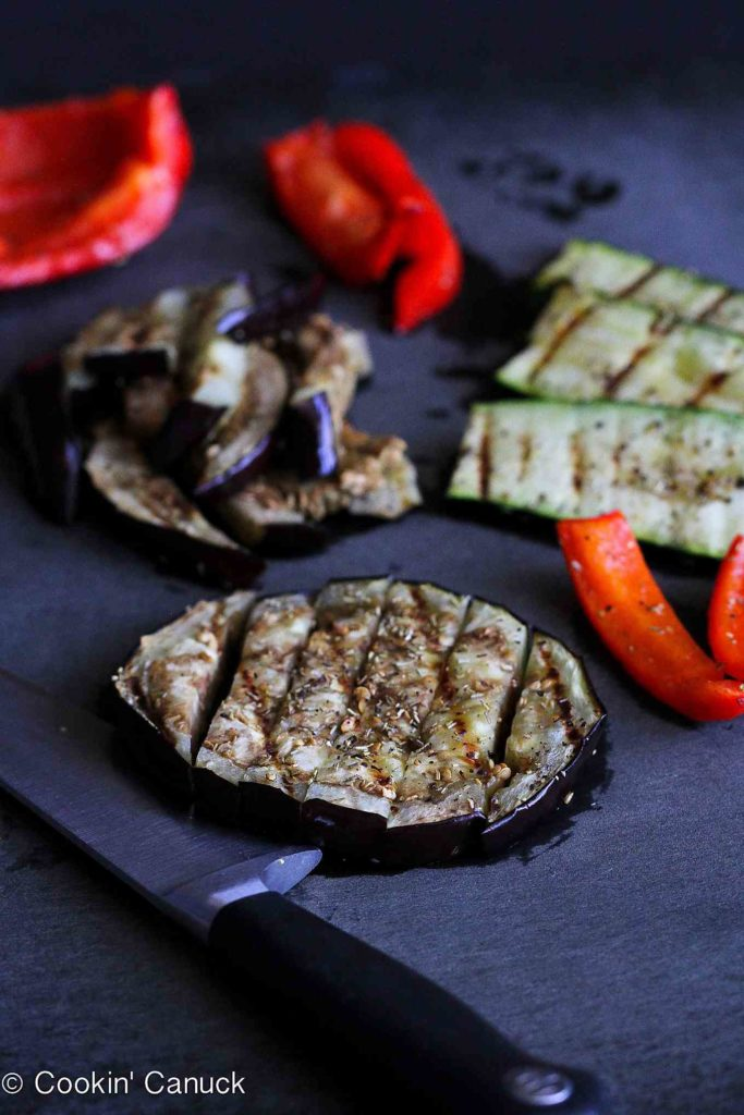 Grilled eggplant, zucchini and red bell pepper on a black cutting board.