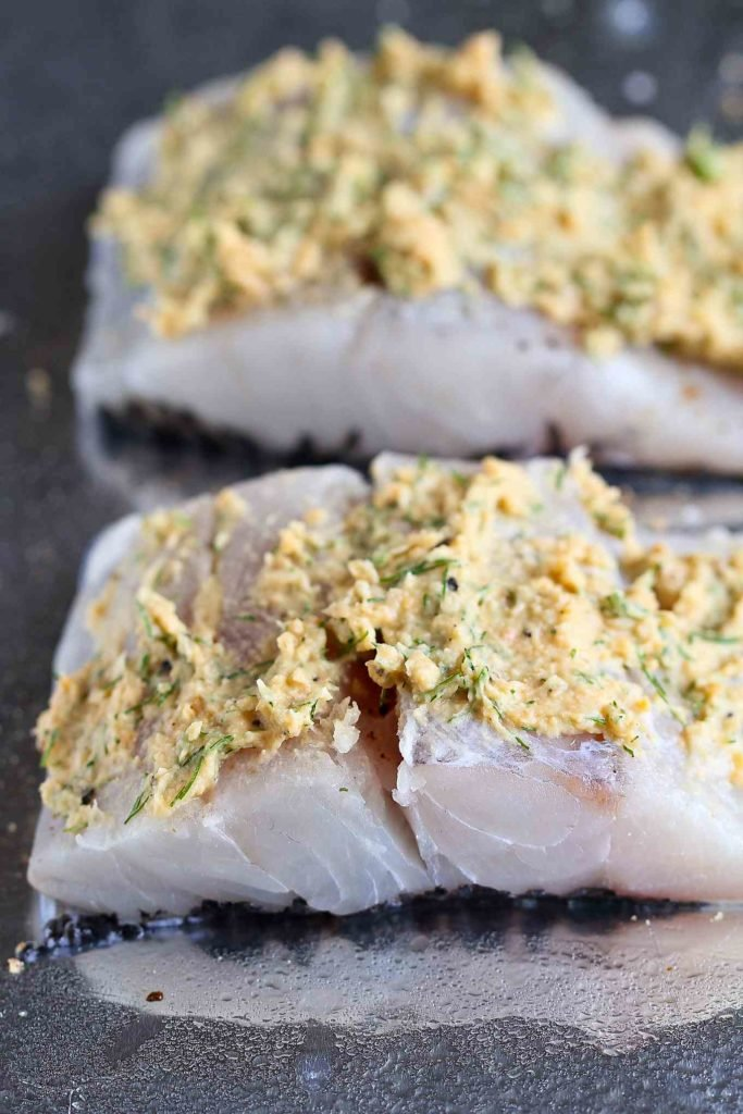 Barramundi (white fish) fillets lined up on a foiled lined baking sheet, each topped with a hummus and dill mixture.