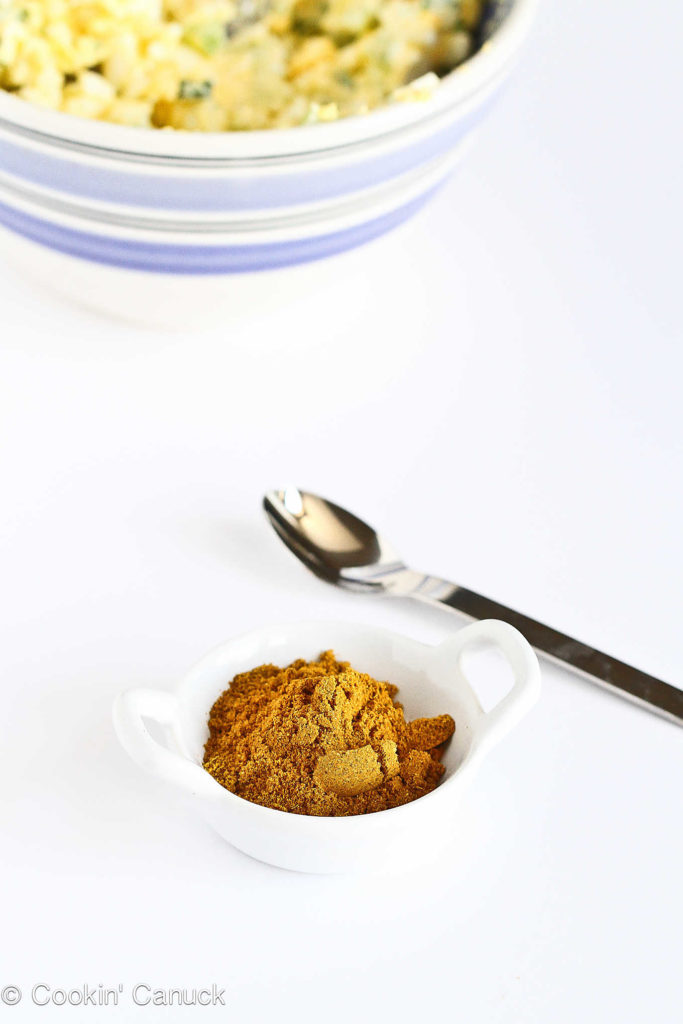 Curry powder in a small, white dish with a bowl of chopped hard boiled eggs in the background.