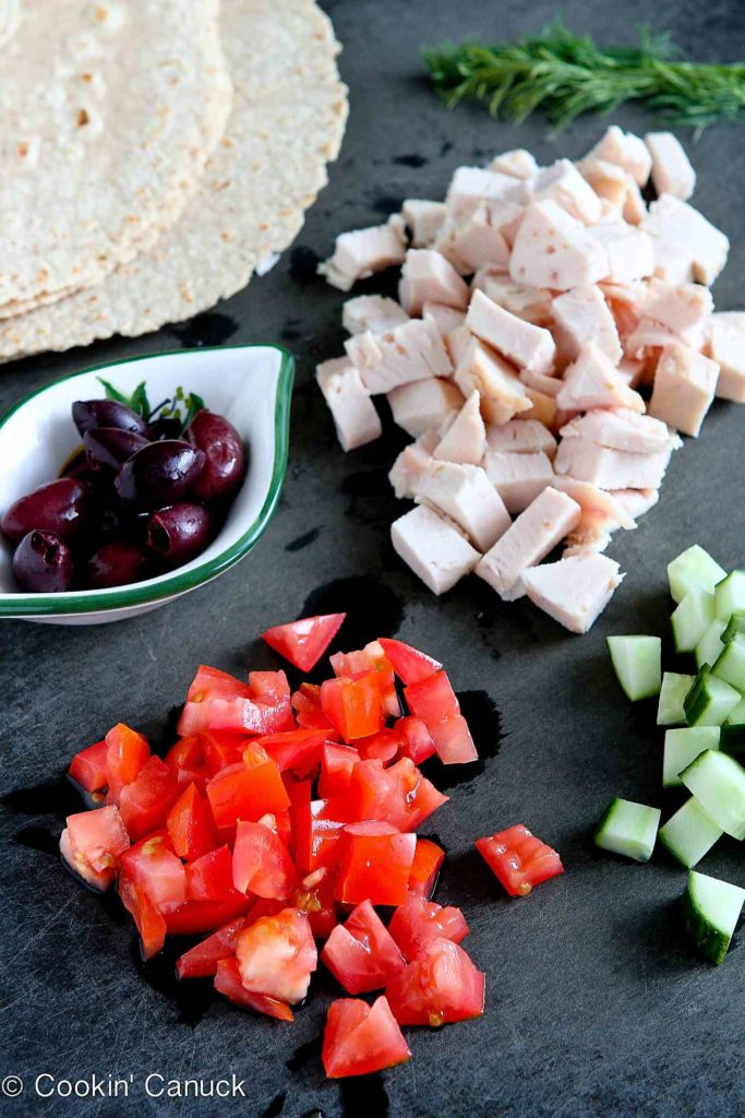 Chopped chicken, tomatoes, cucumber and kalamata olives on a black cutting board.