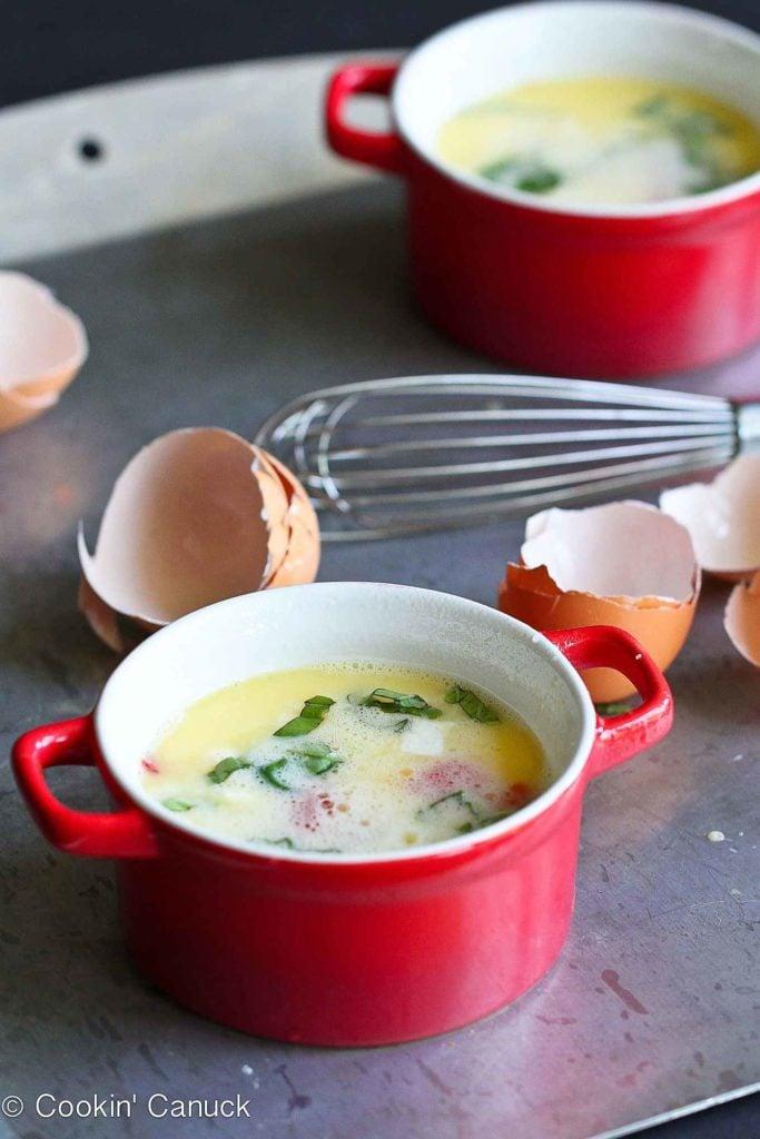 Egg mixture, tomatoes, mozzarella and basil in a ramekin, ready to bake.