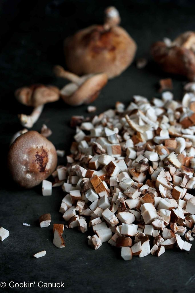 Chopped mixed mushrooms on a black cutting board.