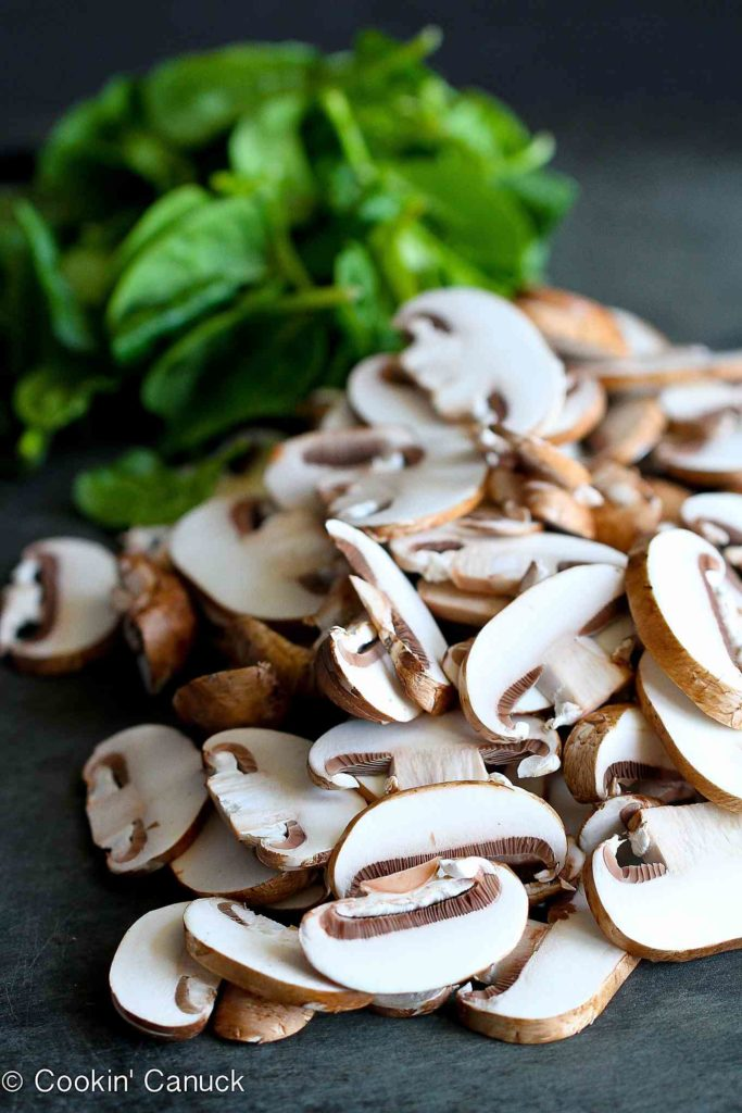 Sliced mushrooms and spinach leaves on a black cutting board.
