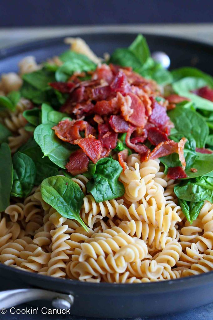 Pasta, spinach and bacon piled in a nonstick skillet.