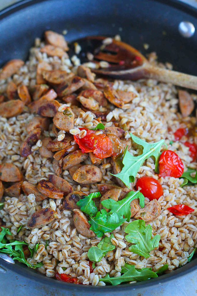 Farro, sausage, arugla and tomatoes, combined in a skillet.