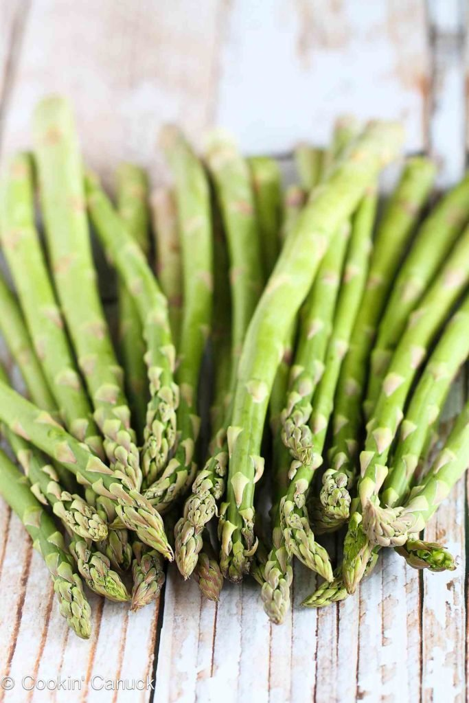 Raw asparagus spears, piled up on a white background.