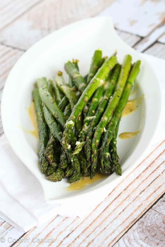 In this roasted asparagus recipe, the fresh springtime vegetable is tossed with olive and roasted until tender, then drizzled with a simple Dijon vinaigrette. 66 calories and 1 Weight Watchers Freestyle SP #weightwatchers #asparagus