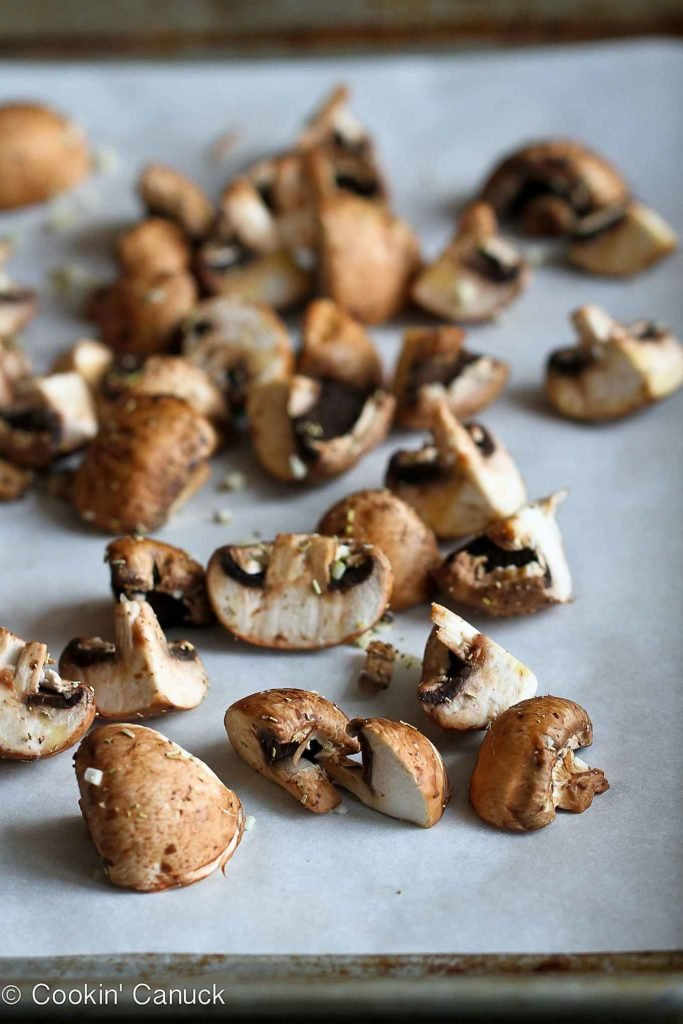 Quartered crimini mushrooms on a lined baking sheet, ready to roast.