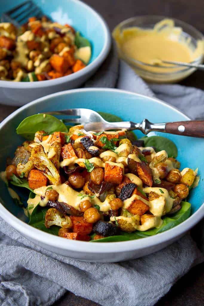 Roasted veggies are like candy - you can't stop eating them! These Roasted Vegetable & Chickpea Bowls are drizzled with hummus dressing and are perfect for a light lunch. 284 calories and 6 Weight Watchers Freestyle SP #weightwatchers #vegan