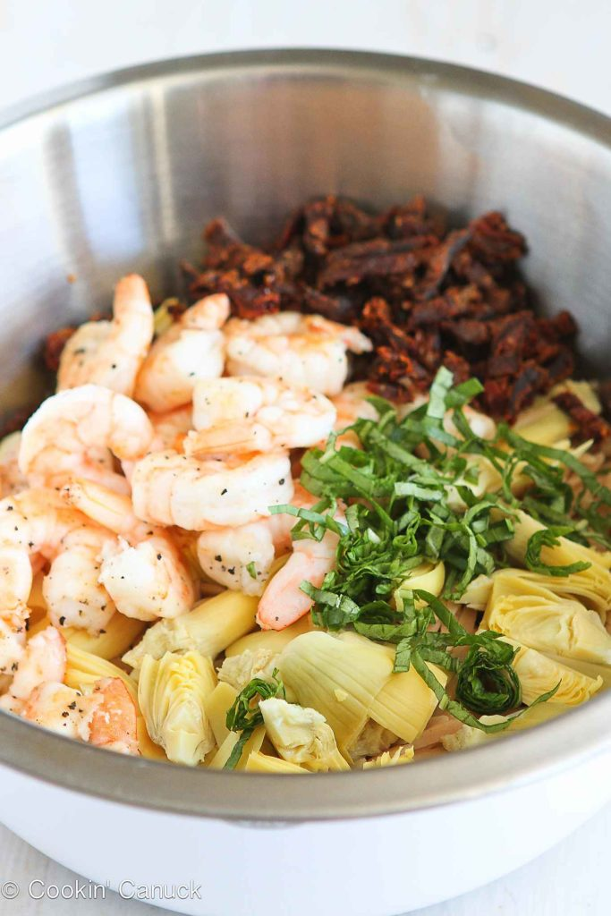 Shrimp, artichokes, sun dried tomatoes and orzo in a large bowl.