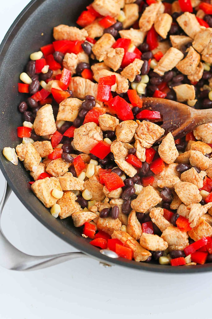 Sauteed chicken breast, black beans and red bell pepper in a skillet.