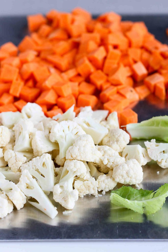 Chopped sweet potatoes and cauliflower florets on a cutting board.