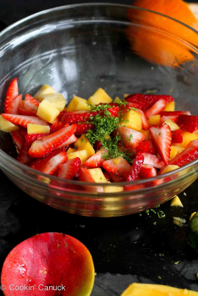 Chopped mango, strawberries and mint in a large glass bowl.